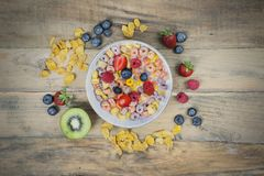 Bowl of cereal and berries on the table. Bowl of cereal and berries with cornflakes on the wooden table stock photos