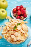 Bowl of cereal on a blue wooden table and fresh strawberry, apple behind. Royalty Free Stock Photos