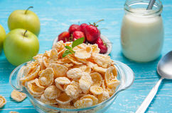 Bowl of cereal on a blue wooden table and fresh strawberry, apple, milk behind. Stock Photography