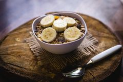 Bowl of cereal with fruit, pieces of banana with oats and cereal. Cereal, seeds and oats, and banana slices, a healthy meal for breakfast or afternoon snack stock photo