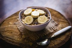 Bowl of cereal with fruit, pieces of banana with oats and cereal. Cereal, seeds and oats, and banana slices, a healthy meal for breakfast or afternoon snack royalty free stock photography