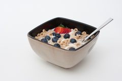 Bowl of Cereal and fruits. Bowl of Cereal with strawberries, blueberries and banana slices Stock Photos