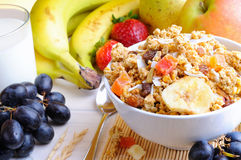 Bowl of cereal and fruits. Bowl of cereal with fruit on a white wooden table and fresh fruits behind Royalty Free Stock Photo