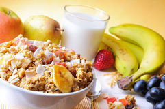 Bowl of cereal and fruits top and diagonal composition. Bowl of cereal with fruit on a white wooden table and fresh fruits behind top diagonal composition royalty free stock photos
