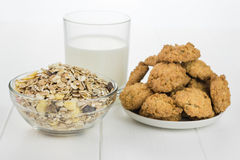 A bowl of cereal, glass of milk and cookies made from wheat flour. Stock Photo