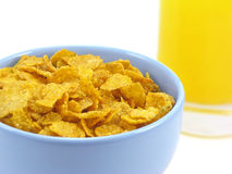 Bowl of cereal and orange juice. Cereal flakes in a blue bowl and a glass of orange juice, on white background Stock Image