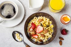 Bowl with cereal rings cheerios, strawberries and milk. Fresh coffee, orange juice and egg. Balanced breakfast concept.  stock photography