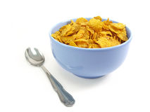 Bowl of cereal with spoon. Cereal flakes in a blue bowl on white background Stock Image