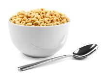 Bowl of cereal with spoon. Bowl of oat cereal with spoon on a white background Royalty Free Stock Photography