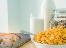 Bowl of cereal with spoon and one glass of milk put on wood table near diabetes textbook and eyeglasses. Calcium food breakfast. Cornflakes and milk concept Stock Photography