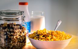 Bowl of cereal with spoon put on wood table near granola in glass container and one glass of milk. Calcium food breakfast. For children before go to school in Royalty Free Stock Photos
