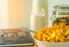 Bowl of cereal with spoon on the wood table on blurred background of glass of milk, bottle, glass container, textbook and eyeglass. Es. Calcium food for Stock Photos