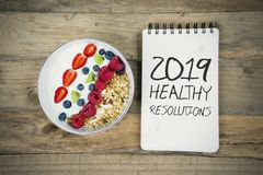 Bowl of cereal with text of 2019 healthy resolutions. Bowl of tasty cereal with text of 2019 healthy resolutions on the table royalty free stock photos