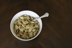 Breakfast cereal in white bowl. Bowl of cereal in white bowl with silver spoon. Isolated on wood table stock image