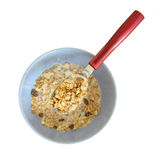 Bowl of cereals. Close up of a full spoon above a bowl with cereals and milk, isolated on white background Royalty Free Stock Photography