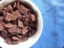 Bowl of cereals. Close view of wheat cereals with chocolate on blue background Royalty Free Stock Image