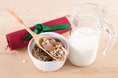 Bowl with cereals, jug with milk and red napkin. Bowl with cereals, glass jug with milk and a red napkin with green ribbon on a wooden table Royalty Free Stock Photography