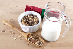 Bowl with cereals, jug with milk, red napkin and scoop on. Bowl with cereals, jug of glass with milk and a red napkin with green ribbon on a wooden table; a Stock Image