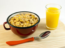 Bowl of cereals and juice. Red bowl of cereals and orange juice on a white background Royalty Free Stock Photo