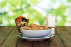 Bowl cereals, nuts, dried fruit, glass  milk on abstract green. Stock Photos