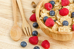 Bowl of cereals with raspberries and blueberrys on a wooden. Royalty Free Stock Photo