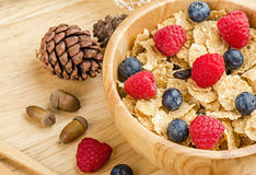 Bowl of cereals with raspberries and blueberrys on a wooden table. Royalty Free Stock Photos