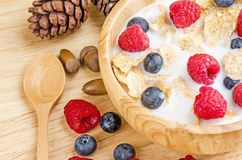 Bowl of cereals with raspberries and blueberrys on a wooden table. Stock Photography