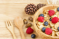Bowl of cereals with raspberries and blueberrys on a wooden table. Royalty Free Stock Images