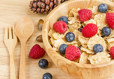 Bowl of cereals with raspberries and blueberrys on a wooden table. Royalty Free Stock Image