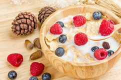 Bowl of cereals with raspberries and blueberrys on a wooden. Stock Images