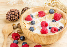 Bowl of cereals with raspberries and blueberrys on a wooden table. Stock Photo