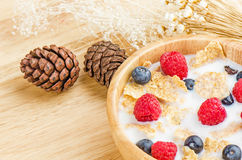 Bowl of cereals with raspberries and blueberrys on a wooden table. Royalty Free Stock Photo