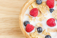 Bowl of cereals with raspberries and blueberrys on a wooden table. Stock Image
