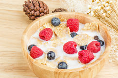 Bowl of cereals with raspberries and blueberrys on a wooden table. Stock Photos