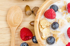Bowl of cereals with raspberries and blueberrys on a wooden table. Royalty Free Stock Photography