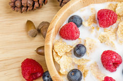 Bowl of cereals with raspberries and blueberrys on a wooden Royalty Free Stock Photos