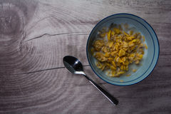 Bowl of cereals with a spoon on wood. En texture stock photography