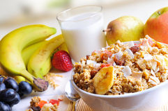 Bowl of cereals top and diagonal composition in kitchen. Bowl of cereal with fruit on a white wooden table and fresh fruits behind in the kitchen. Diagonal stock photos