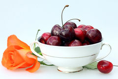 Bowl of cherries. China bowl with ripe cherries and an orange rose Stock Images