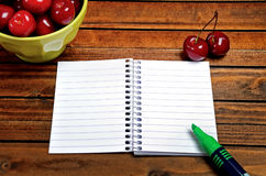 Bowl with cherries fruit and notepad Royalty Free Stock Photos
