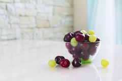 Bowl of cherries on a light table. stock photos