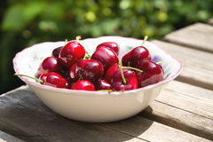 Bowl of cherries. Bowl of red cherries on a wooden table in the backyard on a sunny day Stock Image