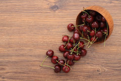 A bowl of cherries. Cherries scattered on the wooden table, healthy snack stock photo