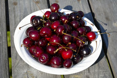 Cherry in bowl. Bowl of cherries on wooden table Stock Image