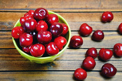 Bowl with cherries on wooden table Stock Photos