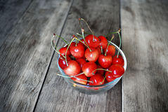 Bowl with cherries on the wooden table Royalty Free Stock Photos
