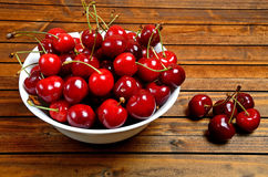 Bowl with cherries on wooden table Royalty Free Stock Photos