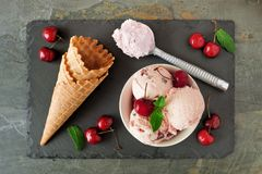 Bowl of cherry chocolate ice cream, above scene with cones on slate. Bowl of cherry chocolate ice cream, above scene with cones and scoops on a slate background Stock Photo