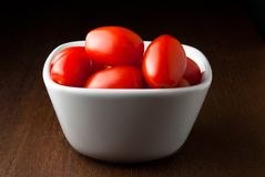 A bowl of cherry tomatoes on a wood table. Stock Image
