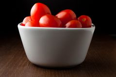 A bowl of cherry tomatoes on a wood table Stock Photography